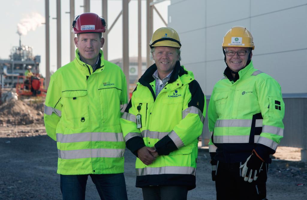 En glad trio som glädsöver det lyckade samarbetet kring det nya fjärrvärmenätet som blir färdigt i oktober. Från vänster Daniel Eriksson- PiteEnergi, Stefan Lindbäck- Lindbäcks Bygg och Magnus Edin- SunPine.  I bakgrunden syns SunPines fabrik som kommer att förse den nya husfabriken med värme.